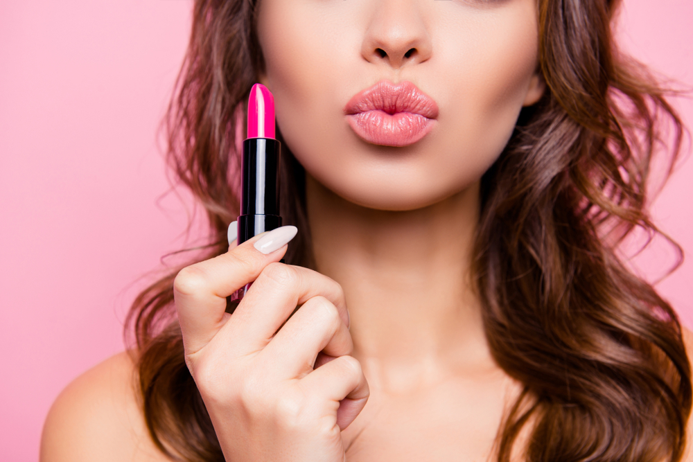 woman with pouty lips holding pink lipstick