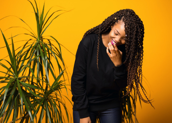 woman giggling and smiling on a yellow background