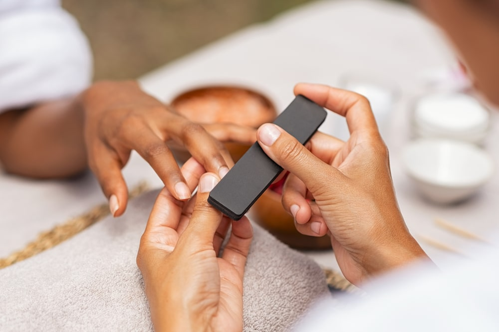 woman getting a manicure and her nails filed