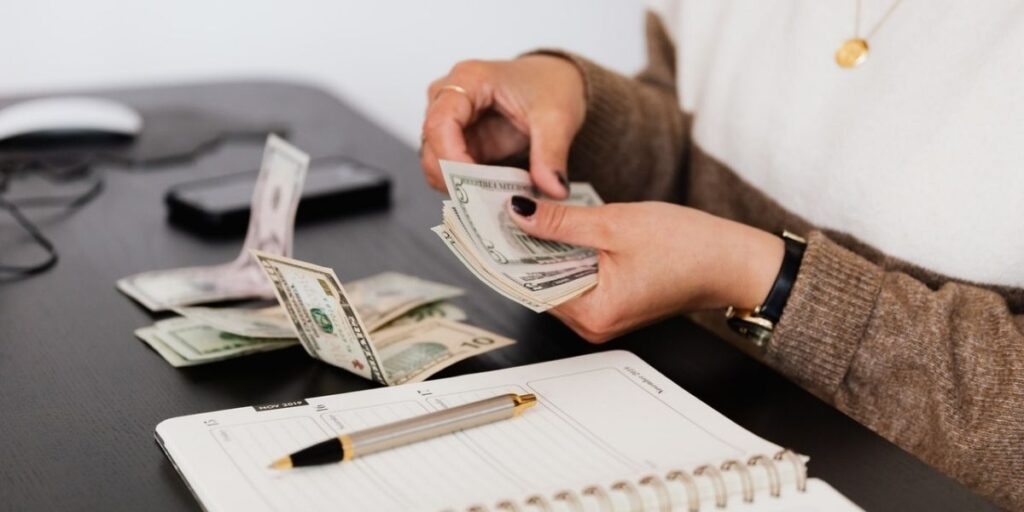 person counting money with a planner
