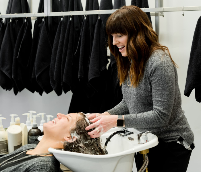 woman washing a client's hair in the salon sink