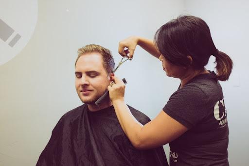 Student cutting man's hair.